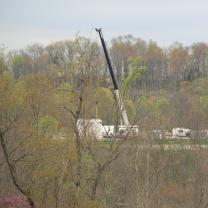 What looks like a crane and extracting equipment within trees in a forest