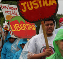 People outside marching holding signs Justica and Libertad