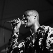 Black and white photo of bald black man smiling and singing into a mic with a flowered shirt on