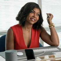 Young black woman smiling and sitting at a desk with computer with one elbow on the desk and arm up by her face in front of a window