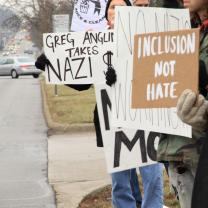 People outside holding signs that say Inclusion Not Hate and Greg Anglin takes Nazi Money