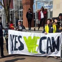 People holding a Yes We Can sign outside a brick building
