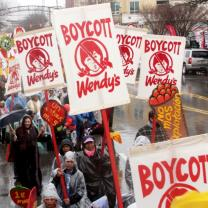 People marching in the rain with Boycott Wendy's signs