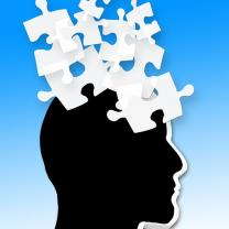 Black silhouette of a head facing right with white puzzle pieces flying out of his head against a blue background
