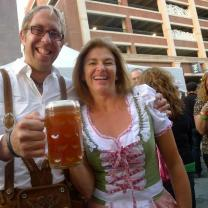 White ma with gray hair and glasses smiling holding a huge mug of beer with a woman who is wearing a German-looking corset and frilly top