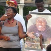 Black woman talking and pointing to photo of her son, young black man