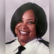 Head shot of black woman with short black hair smiling wearing a police uniform