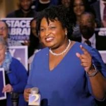 Older black woman with short curly black hair, white pearl necklace, blue dress, standing and smiling while gesturing in front of lots of people holding signs that say Stacey Abrams