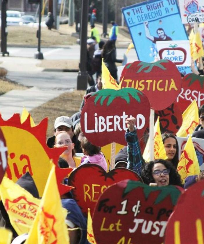 People holding bright red signs shaped like tomatoes that say Justica and Libertad