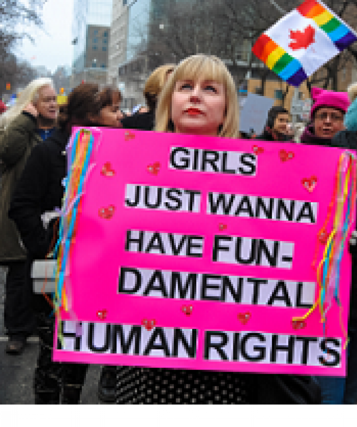 Women marching and young blonde woman holding a pink sign that says Girls Just Want to Have Fun-damental Rights