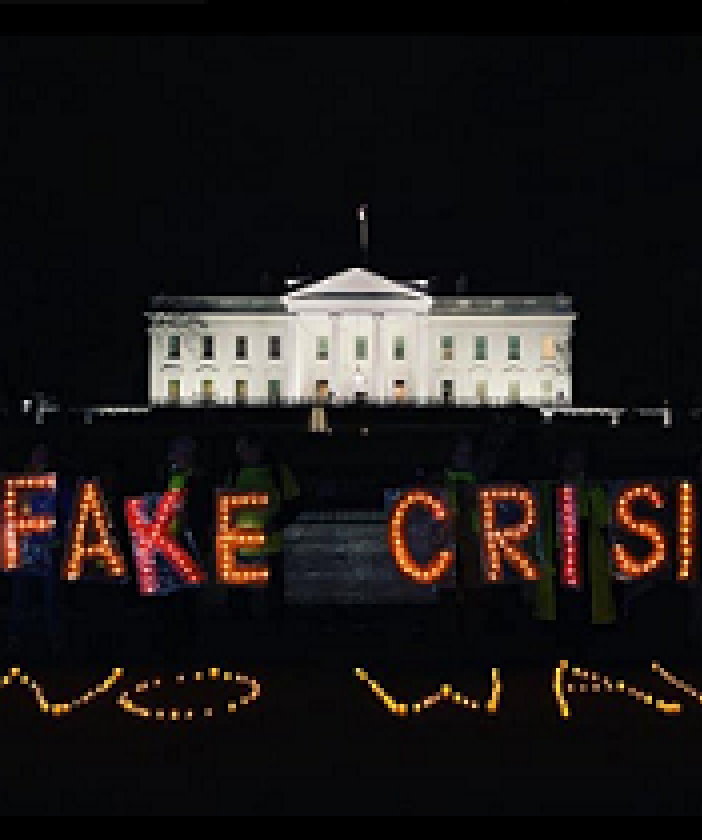 PHoto of white house with neon lights in front against black saying FAKE CRISIS NO WALL