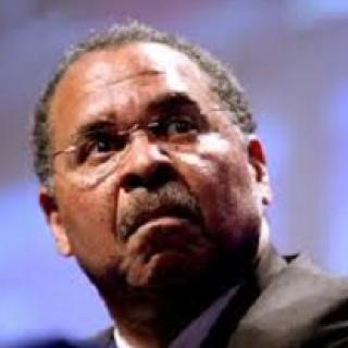 Close up of black man's face with wire rimmed glasses, a moustache and a worried or scared look as he looks up