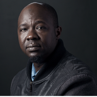 Middle aged black man, bald, in grey sweater, looking at the camera like he's a bit sad and a bit let down