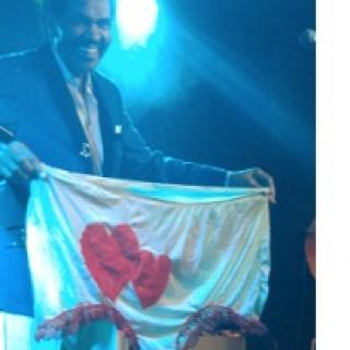 Smiling black man standing in a suit on a stage holding up a huge pair of women's undies that are white with two red harts on them
