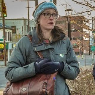 Young woman with brown rimmed glasses, long brown hair in winter clothes outside with her purse over her shoulder an holding it close to her body, looking like she is talking
