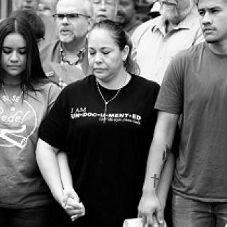 Black and white photo of three Latino people, a young girl with long brown hair looking down, a middle-aged woman with a black T-shirt and necklace looking down and a young man looking very worried, all holding hands with several people behind them