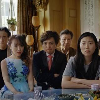 Very serious faced Asian people posing at a table all dressed up