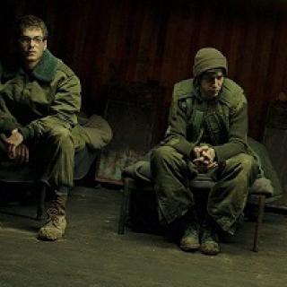 Two young white men in military uniforms sitting dejectedly on a bench