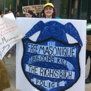 Woman holding a huge sign with a police badge that says Free Masonique Cbus Cops Kill