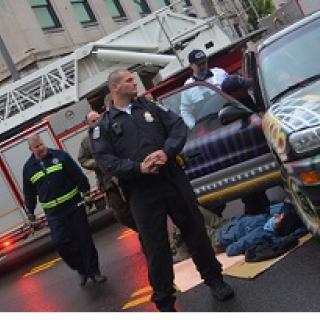 Cops and person lying on ground next to a car with a fire truck