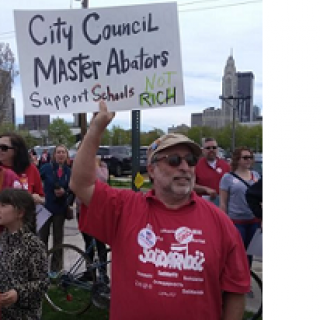 White man with sunglasses, a gray beard and a baseball cap wearing a Solidarity T-shirt is outside among lots of people with downtown Columbus in the background, holding a sign that says City Council Master Abators Support Schools not the Rich