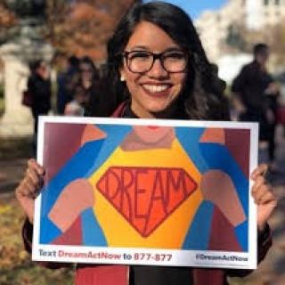Young smiling woman with long black hair and big black-rimmed glasses holding a bright colorful sign that says DREAMER on it