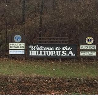 Long outdoor sign in front of trees saying Welcome to the Hilltop USA