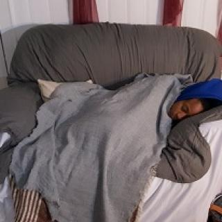 Young black woman asleep under huge blanket on a gray loveseat