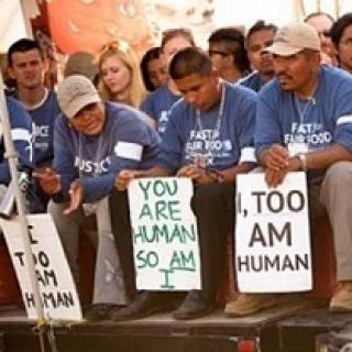 Latino men wearing blue shirts sitting and holding signs that say I Too, Am Human