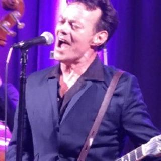 White man at a microphone belting out a song wearing a dark suit and shirt unbuttoned with a guitar strapped around him