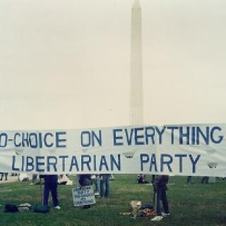 A long sign saying Pro choice on everything Libertarian Party held outside in front of the Washington monument
