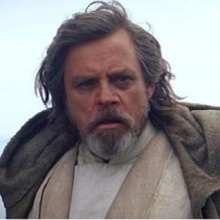 Older man with unkempt gray long hair and a beard looking intensely at the camera wearing a cape
