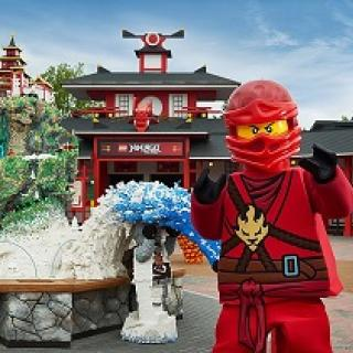 Robot looking character in red suit and helmet standing by and in front of structures made out of legos