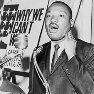 Black man speaking at a mic wearing a suit, with a sign in the background to his left saying Why We Can't