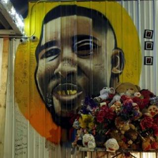 Painting of a black man's face against a yellow and orange circle on a white sided building with a bouquet of flowers in the foreground