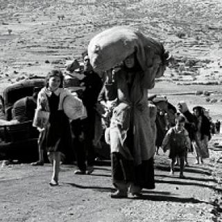 Black and white photo of women and children walking down a dusty path outside with the woman in the foreground carrying a big heavy bag on her head