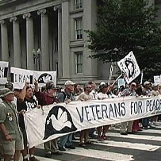 People holding a banner that says Veterans for Peace standing in front of a government building