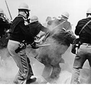 Black and white photo of police wearing helmets with their backs to the camera, looking like the are beating people with sticks among a lot of gas in the air obscuring the people in the picture