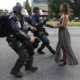 Young black woman in long flowing black and white dress wearing glasses standing straight and tall and calm and two older white heavily armed riot police looking like they are stepping back away from her