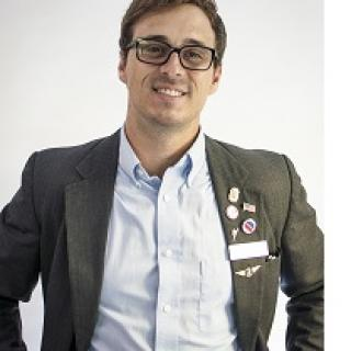 Young white man with dark rimmed glasses and a suit with lots of political buttons and a big smile