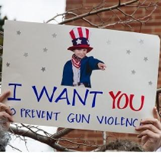 Someone holding up a sign with a picture of a young boy dressed like Uncle Sam and the words I WANT YOU to prevent gun violence
