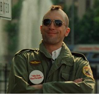 Robert De Niro, youngish white man with a mohawk hairsut and sunglasses smiling with his arms crossed, wearing an army jacket with patches