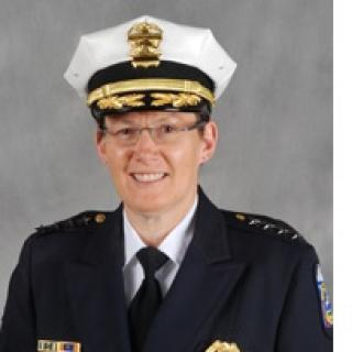 White woman in a police uniform and wire rimmed glasses smiling and posing
