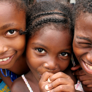 Little black girl with braids with two other black kids