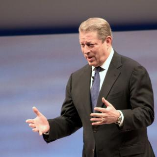 White man with graying dark hair in a suit holding his arms out in emphasis as he talks