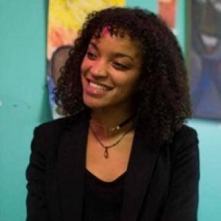 Young black woman smiling turning her head to the left wearing a black suit against a colorful wall of art