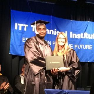 Black man in graduation robe and hat receiving diploma