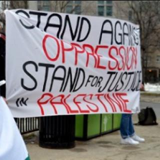 A big sign on a sheet saying Stand Against Oppression Stand for Justice for Palestine
