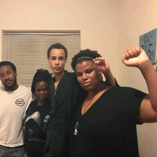 Four young black people one with fist in the air
