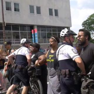 Police al suited up with helmets and bikes attacking stationary black people with black tape over their mouths